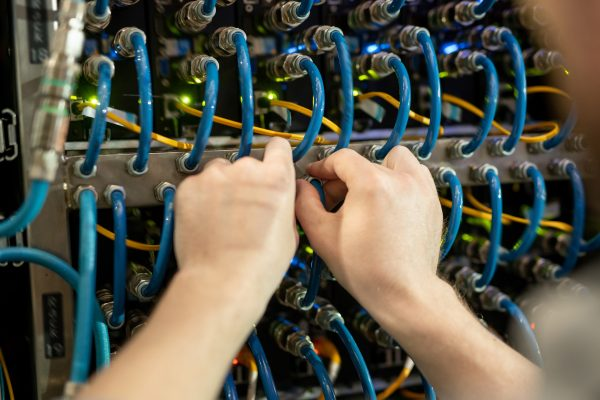 Close-up of unrecognizable server support specialist checking cables of switchboard while examining server, copy space